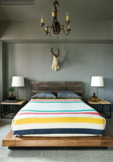 """The colors of the blanket on the master bed in the city may look straight out of the groovy """"70s, but they harken back to a couple centuries before that. In the 1770s, Stanton explains, fishermen would trade these traditional wool blankets to Native Americans in exchange for furs and other goods. Here, its vivid stripes help temper the deep gray walls and the rustic touches found throughout the space. Rugged platform bed, Stanton Home Furnishings."""