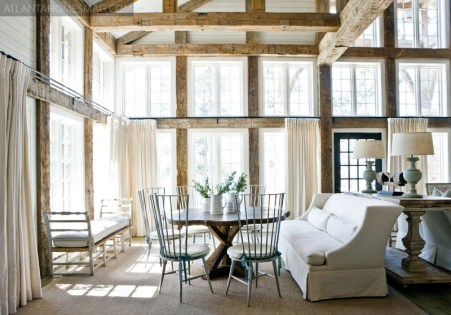 "The large main living space, defined by reclaimed wood beams that frame the windows overlooking Lake Martin, is divided into smaller, more intimate seating and dining areas by the towering fireplace. ""The homeowners wanted to have areas to do different activities and for different people in the family,"" explains designer Paige Sumblin Schnell, principal of Tracery Interiors."