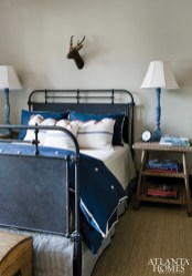 Layered in shades of blue from the iron bed and linens to a pair of wooden table lamps the mood in the second country chic guest room is kept lively with a petite deer head.