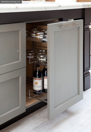 Weathered-gray oak cabinet doors on the island provide contrast to the kitchen's other finishes in cream and mahogany.