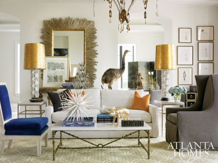 """""""We wanted to have a surprise in every room,"""" says Melanie Turner of this high-rise condominium she designed at The Residences at The St. Regis Atlanta. In the spirit of adventure, she included vintage taxidermy in every space. In the living room, she placed a tailored white sofa between a skirted armchair and an Oly Studio side chair covered in cobalt velvet. Midcentury lamps adorned with bells add sculptural interest, while gleaming shades, a midcentury Italian starburst mirror, brass coffee table and goldleaf pig add sparkle."""