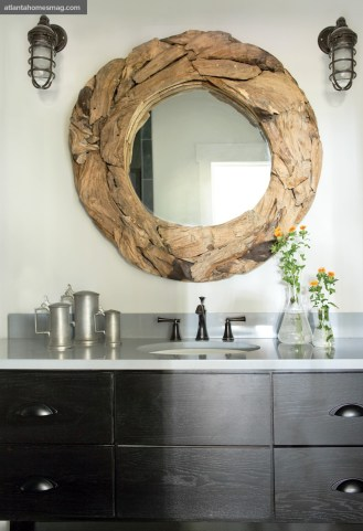 The petite powder room brings elements of Stanton's favorite vacation locales into one space; a round driftwood mirror mixes with industrial factory lights-turned-sconces and even more of his favorite pewter.