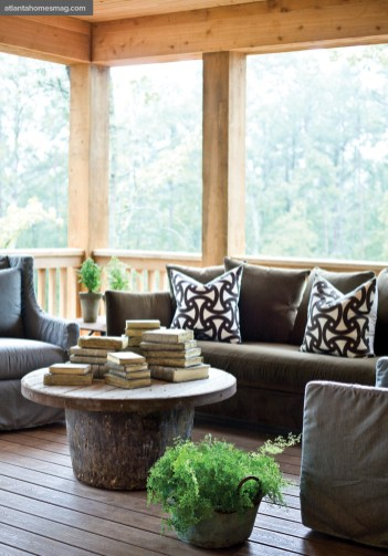 An inviting seating nook on the main-level porch that utilizes Lee Industries' virtually indestructible collection of slipcovered outdoor furniture can more than stand up to the elements, notes the designer. The sofa, covered in a velvet-like Sunbrella fabric, is accented by brightly colored outdoor pillows and hand-cast concrete books, all of which are available through Stanton Home Furnishings.