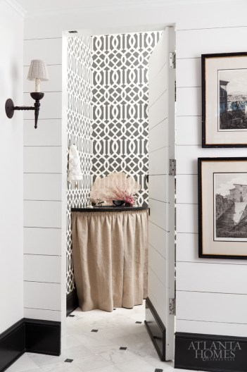 "The powder room—with ""Imperial Trellis"" wallcovering by Schumacher covering the walls—is hidden behind a jib door."