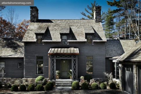 This D. Stanley Dixon-designed New England colonial-style cottage features hallmarks such as wood paneling, wood shingles and classic dormers, but the architect imbued a North Carolina aesthetic with fieldstone chimneys, a copper awning and dark exterior paint.