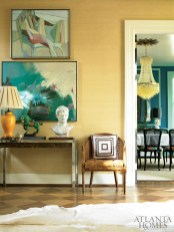 "Against a backdrop of grasscloth wall covering, fine art and vintage collections welcome guests in the home""s foyer."