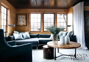 """The aptly named """"reading room"""" has plenty of spots upon which to lounge, including Bradley Hughes, Brooks Chair, upholstered in a Christian Fischbacher fabric. A round wood-and-metal table draws the walls— honey tones into the center of the room."""