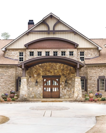 The Pearsons enlisted Ruben Calleiro to create a Montana-style home on their lakeside retreat; the builder worked with Pella and DoorSmith to custom-design the front door and matching his-and-hers garages to establish a commanding entrance to the home.