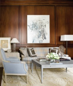 Clean-lined furniture, modern lamps and a painting by artist Jimmy O'Neal provide contemporary counterpoints to the study's traditional paneled walls. Brown chose a Rogers & Goffigon blue-gray plaid fabric for the sofa, a nod to the husband's English roots. The artwork on the side table is by Tom Swanston.
