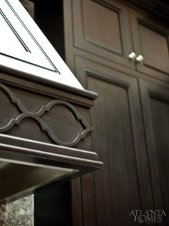 A carved detail on the range hood surround echoes the tile pattern found in the backsplash.