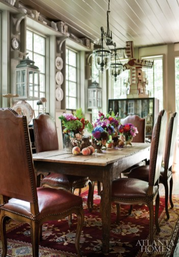 A large windmill from Holland and a diorama of a Scottish loch retreat add interest and fun to the finer antiques displayed in the dining room. The lush flowers on the dining table are repeated in floral motifs throughout the house, including in Oriental rugs, draperies and even needlepoint.