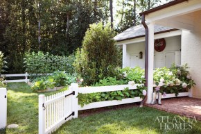 """In front of the estate's gun house—which contains a living area, bar, office and recreation room—is a vegetable garden. """"One of the biggest compliments we've received from friends of Mrs. Carr is that she would have loved what we did,"""" says the homeowner of the property's meticulously designed gardens, which she """"inherited"""" from of one of Atlanta's most devoted horticulturists, Anne Carr."""