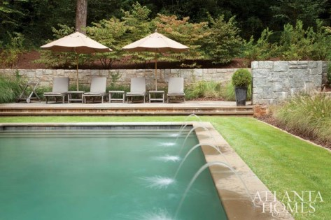 Beyond the stone wall, the formal pool area gives way to the natural forest. The landscape design is by John Howard of Howard Design Studio.