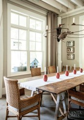 In the dining area, an old worktable set on saw horses can easily accommodate 12 at mealtime. Designer Jeff Jones repurposed a baler rake to create a candle-lit chandelier that's raised and lowered with vintage pulleys.