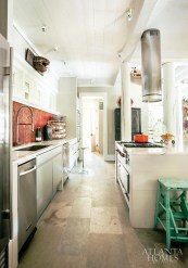 """The kitchen is outfitted with modern amenities, including aluminum Siematic cabinets, Calcutta Gold marble countertops, a Sub-Zero refrigerator, Wolf range, Futuro hood and Gaggenau ovens. Still, there are primitive pieces, like """"Charlie Catfish,"""" who oversees the room, that beautifully balance old and new."""