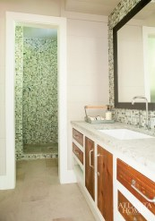 A guest bath features glass tile in watery colors with wood-faced cabinetry giving a nod to the nearby Chattahoochee National Forest. Italian limestone floors run throughout the house, except in the bedrooms, where there's reclaimed heart pine.