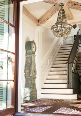 """The homeowners credit builder Christian Tennant for executing the intricate building plans of their Rosemary Beach vacation home, including the inlayed floor and beautiful wood molding in the foyer. """"With all the detailing, the entry immediately makes you feel like you're somewhere special,"""" says residential designer Rick Spitzmiller. The Oly Studio chandelier, made of petite abalone shells, is from Bohlert Massey Interiors. The blue-gray Swedish antique clock is from Parc Monceau."""