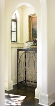 A tall iron console table fills an architectural nook to the left of the front door, providing a pleasing place for the eye to land.