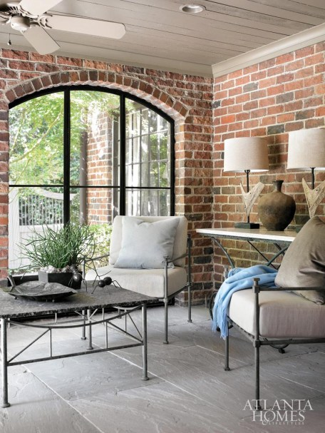 Just beyond the living room, a covered patio is accented with elegant iron furniture from Niermann Weeks, which Kay and Hooff recovered in a fresh fabric. The lamps and console table are from Peachtree Battle Antiques.
