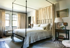 """In the master bedroom, a 17th-century reproduction Italian iron bed by Gregorius Pineo takes center stage. The white-on-white crewel fabric is by Old World Weavers. The lamps were designed from late-19th-century oak carvings. """"I have so much respect for the heart and soul Susan puts into every interior,"""" Prillaman says. """"We had total trust."""""""