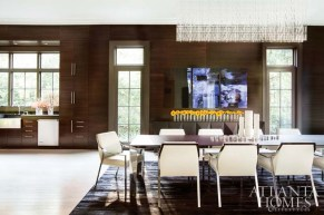 "The dining area of the 60x19 space features a custom 12-foot-long table by Molteni & Co. ""There is only one in the world this long and it's at their house,"" says designer Joel Kelly. Chairs, Holly Hunt. Cowhide rug, Stark. In a nod to Melissa's beloved New Orleans, the Rathbuns refer to the color of the bleached and pickled floor as ""Gumbo."""