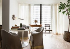 Within the living room, a Saarinen table surrounded by three gray-and-gold slipcovered chairs by John Saladino creates a mini-library area, visually anchored by an antique Italian sconce on the nearby wall. The desk lamp is a midcentury design by George Nelson. The paint color is Cloud White by Benjamin Moore.