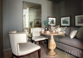 Ingram selected overscaled upholstery for the diminutive dining area—chairs from Mrs. Howard and banquette-style seating created with a Mitchell Gold + Bob Williams sofa. An antique mirror bounces light into the dramatic space, one perfectly suited for snacks and cocktails. A West Elm table is set with Paris porcelain from the 1850s, while hand-colored prints featuring great oak trees of England surround the alcove. The space is painted in Benjamin Moore's Cromwell Gray HC-103.