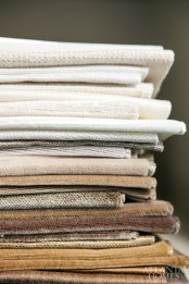 A neat stack of neutral fabrics in various textures.