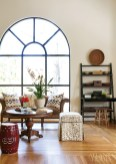 """Arches are one of my favorite architectural elements,"" explains Bentley. Black lacquer Asian-inspired bookcases flank the window and sitting area."