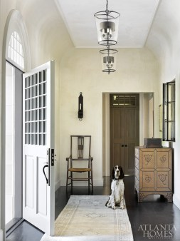 Rounded walls and interior windows create depth and history in the entry gallery. The studded chest is by Formations at Jerry Pair, the antique accent chair was found at The Stalls on Bennett Street and the iron sconces and glass pendants are by Ainsworth-Noah.