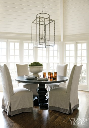 A patinaed lantern from Ainsworth- Noah makes an eye-catching display in the intimate dining room; a round table from South of Market holds court beneath a cathedral ceiling. In the place of window treatments, Linen slipcover chairs from Bungalow.