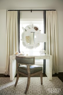 For a space overlooking the back porch in the master bedroom, Morris dressed up the homeowner's vanity by Mrs. Howard with a chair from B.D. Jeffries and a white plaster mirror from South of Market.