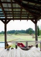 On a hot August day, Atlanta landscape designer John Howard relaxes on a hammock strung across a shaded, Southern-style wraparound porch at Keith Summerour's Towerhouse Farm. A friend, collaborator and distinguished guest at this fate, Howard also helped design the cypress allee that now borders Summerour's sunflower fields, which can be spied in the distance beyond a dry stone hedge.