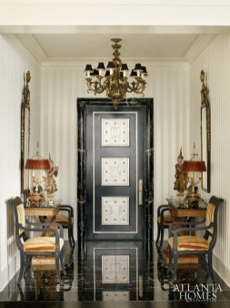 A custom inlay door by Calhoun Design & Metalwork, high-gloss fluted paneling and marble floors fashion a dramatic entry, complete with identical arrangements of gilt consoles topped with Mandalay period teak wood temple dancers, 19th-century walnut mirrors and chairs covered in a gold velvet stripe by J. Nelson.