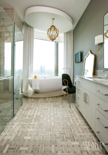 Capitalizing on views of the Atlanta skyline, the master bath boasts an elliptical tub on a marble platform that points toward Buckhead. The room's hard surfaces are softened by simple curtain panels and a curious vanity chair covered in Persian pony hair. The Moroccan-inspired gold leaf ceiling fixture is by Cyan Design. The basket-weave Silver Wood floor tiles are by Porcelanosa.
