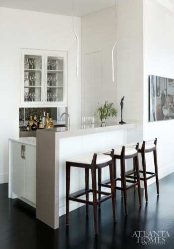 The wet bar, adjacent to the living/dining space, is enhanced by serpentine chrome pendants from Illuminations. Custom nickel-back bar stools by Bjork Studio.