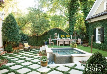 """The verdant and perfectly manicured backyard features Mondo grass-accented lattice stonework, a luxurious soaking pool and a spread of artificial turf, which stays lush despite the lack of sunlight. It's made """"a world of difference for us,"""" says Debra about the material, which helps maximize the space to its fullest potential."""