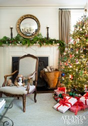 Aglow from the light of the Christmas tree, the family room offers a warm welcome thanks to Ervin's dog, Bunny, and festive touches of red and green.