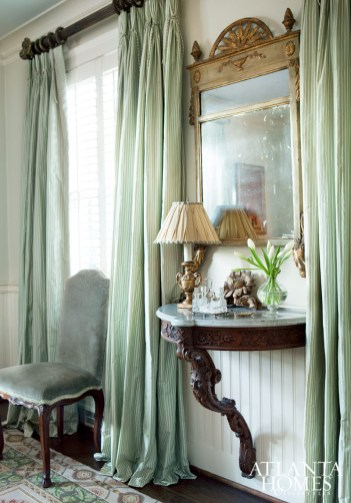 Sumptuous silk curtains and grey linen-velvet chairs give the dining room Old World appeal.