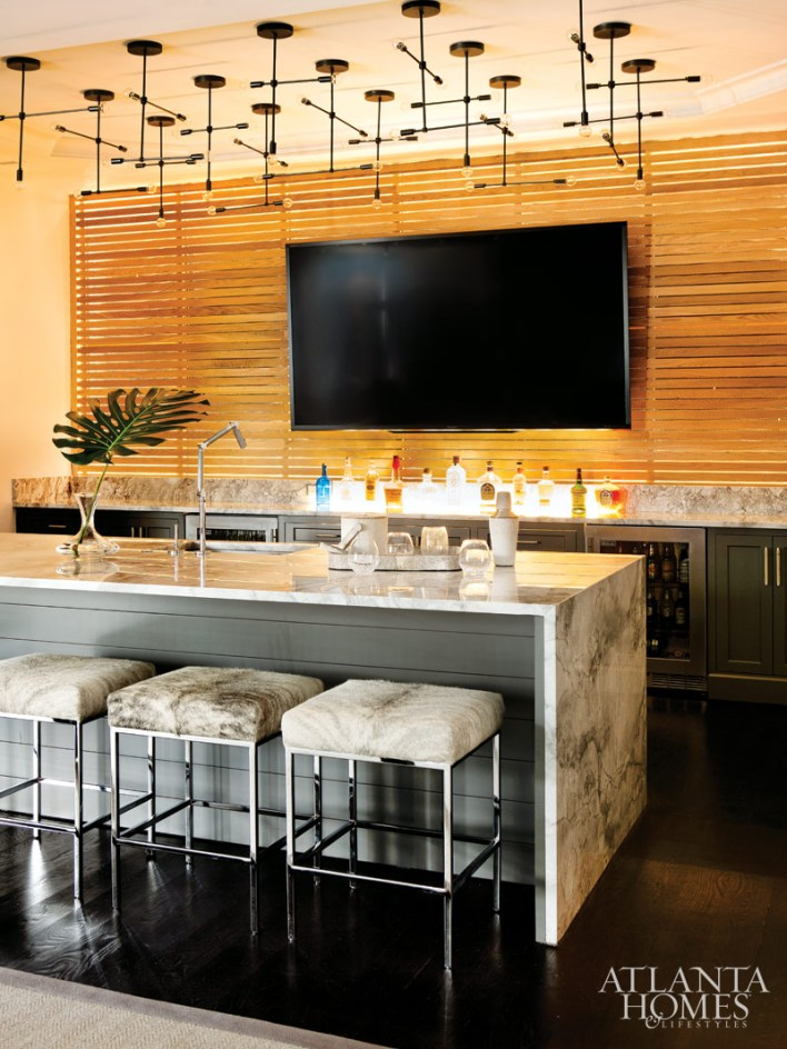 The bar, with its backlit wall, gives the Ugglas a glamorous space to entertain friends. A custom light installation by GREY Furniture lends drama to the space.