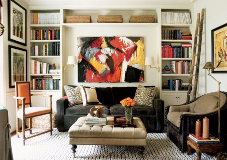 """The den exudes warmth and is one of Giles"""" favorite spots. Art above sofa, Will Kay, Carter Kay Interiors, (404) 261-8119. Stacked paintings, Katie Walker, Sandler Hudson Gallery, (404) 817-3300. Art above chair, Allison Stewart, Sandler Hudson Gallery. Wicker chair, Wicker Works, Jerry Pair, ADAC, (404) 261-6337. Orange chair, Paul Ferrante, Ainsworth-Noah. Sofa, The Charles Stewart Company. Custom ottoman/coffee table, Courtney Giles Interiors, Corn Upholstery, (770) 491-9368."""