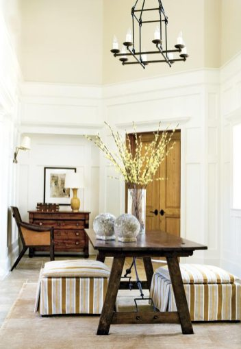 The two-story foyer provides a comfortable atmosphere in which to greet guests. Twin Marie ottomans covered in Cowtan and Tout Rio Tabac fabric, Bradley Hughes, flank an antique Spanish table from Stalls at Bennett Street, (404) 352-4430. A geometric iron chandelier, Max & Co., (404) 816-3831, sheds light on stone balls, South of the Market, (404) 995-9399.
