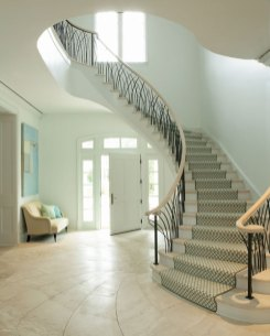 Contributing a sense of drama to the entry way is the nautilus motif Roberts designed for the limestone floor and the wrought-iron railings handcrafted to imitate the marshy blades of grass just outside the windows. Iron work by Andrew Crawford.