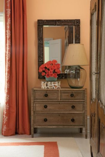 Roberts believes in anchoring bedrooms with antique armoire, which in this case hides a TV. Flanking the armoire are a carved pine mirror and English chest.