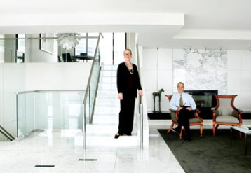 Ann and Ben Johnson love the fact that three levels give their penthouse dimensions that make it feel larger than its 3,500 square feet. On the main level, a pair of Biedermeier chairs forms a traditional contrast to the living room's classic contemporary furnishings and art, including a sculpture by George Mallett.