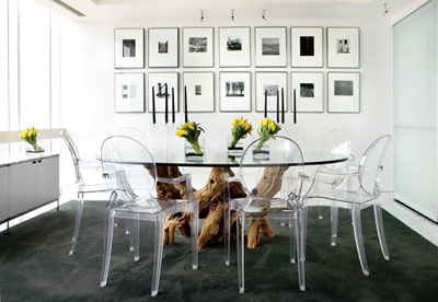 The penthouse's versatile layout is great for entertaining. Sliding glass doors, right, lend a partition between the kitchen and dining room, where Philippe Starck Ghost Chairs surround a glasstop table with a cypress-stump base. On the wall is a collection of photographs by Harry Callahan, Ralph Eugene Meatyard and Walker Evans.