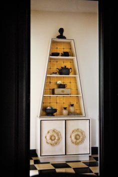 A mid-century obelisk-shaped cabinet features a collection of 19th-century Wedgwood basalt.