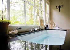 Natural light floods into the space surrounding the soaker tub, while the tree canopy beyond provides privacy.
