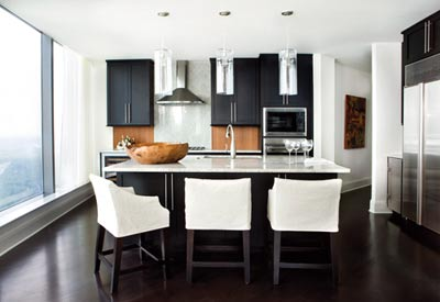 """Minimalism and comfort reign in the contemporary kitchen, where Westbrook""""s team selected granite countertops and sleek, espresso-colored cabinetry from a range of options available to Sovereign residents. The modern glass pendant lights are from South of Market."""