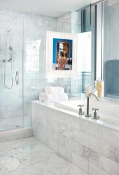 """Westbrook took an unusual approach in the bathroom, suspending framed photography directly in front of the shower""""s glass enclosure. It serves as a strong focal point, second only to the views of Buckhead below."""